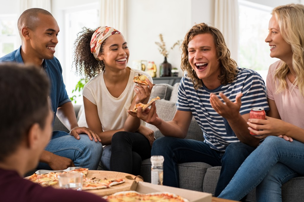 Friends get together while eating pizza