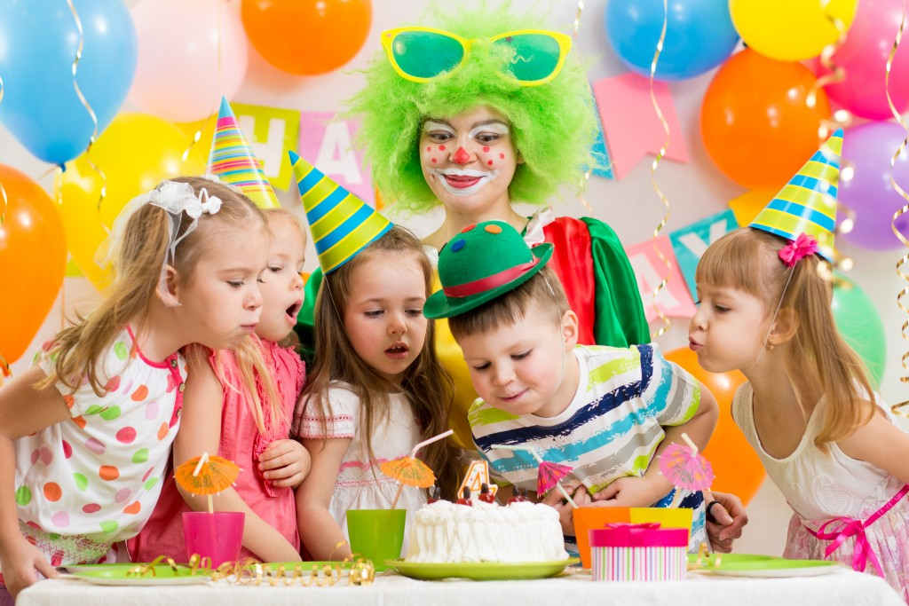 kids at a birthday party blowing birthday cake