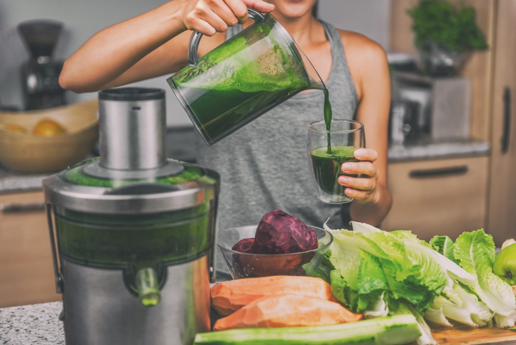 woman juicing vegetables