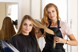 Beautiful blonde female hairdresser holding scissors