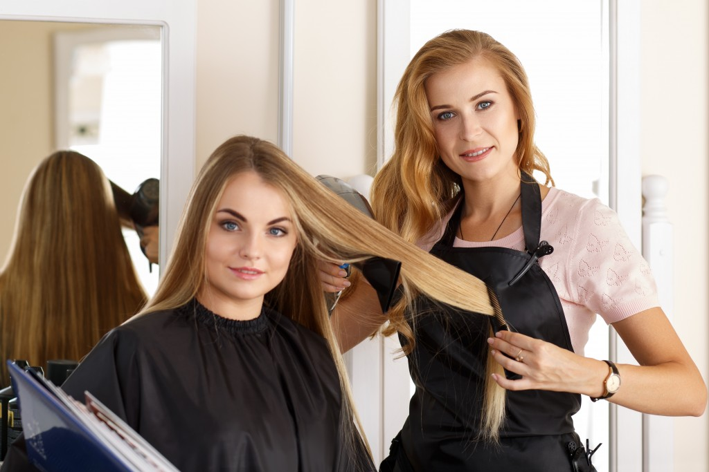 Beautiful blonde female hairdresser holding scissors