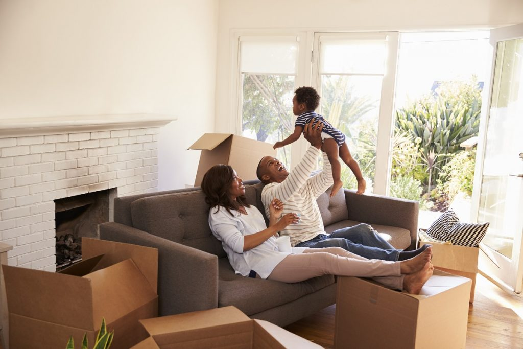 Family-who-just-moved-in-their-new-house-surrounded-by-boxes