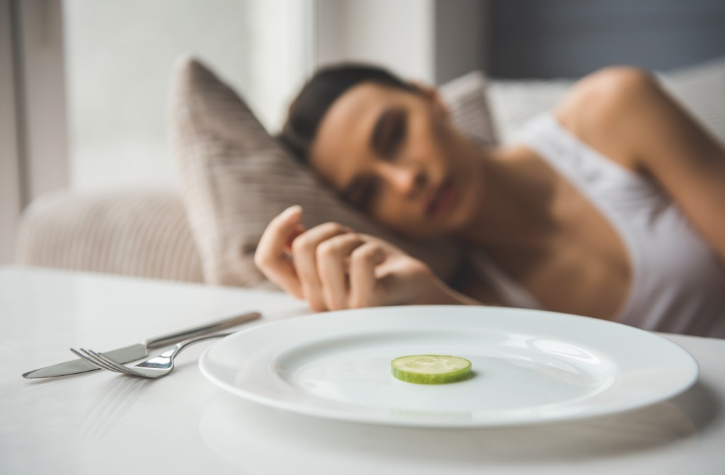 Woman struggling to eat, cucumber on a plate