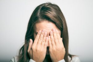 frustrated woman covering her face