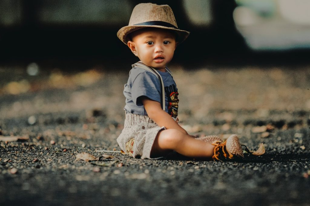 toddler boy wearing hat sitting on the ground