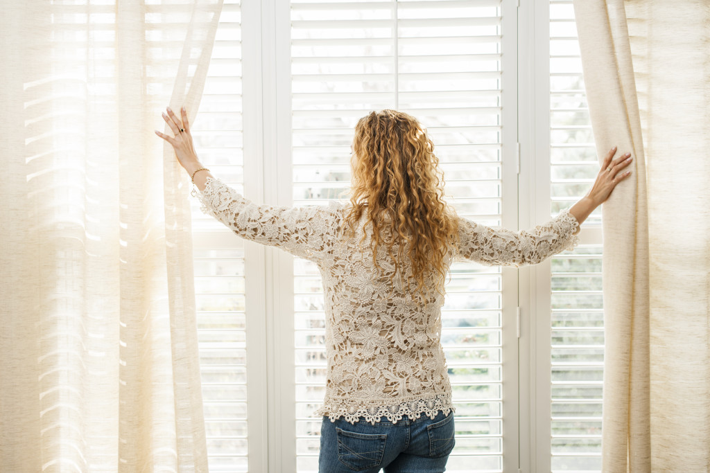 woman standing next to the windows