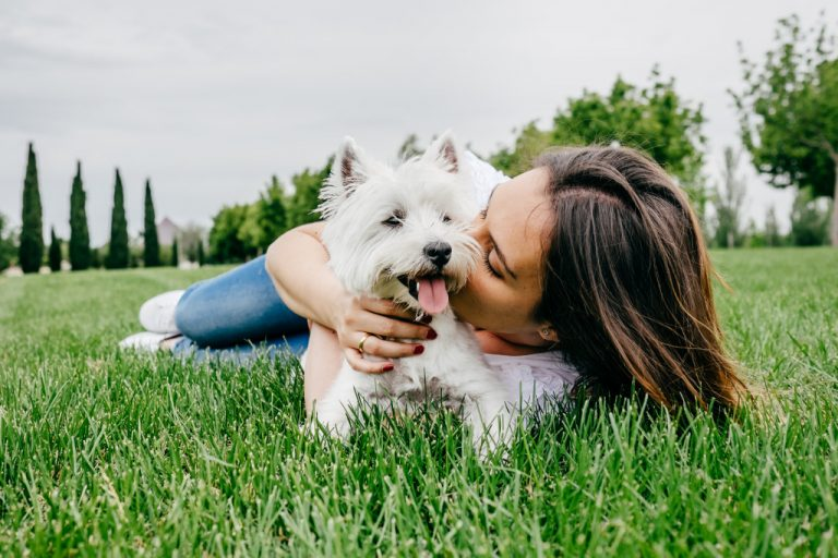 woman cuddling with pet dog